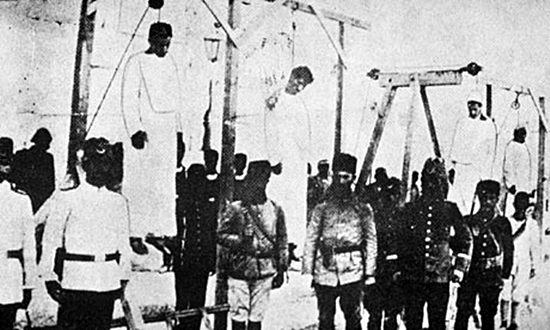 Ottoman soldiers pose in front of hanged Armenians