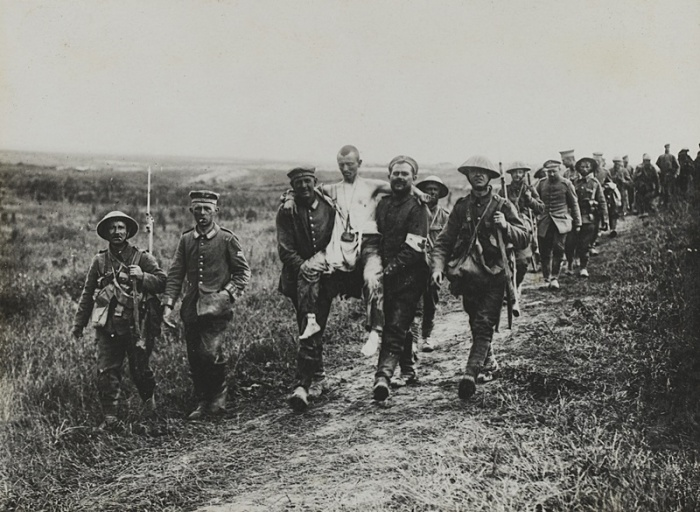 British soldiers with wounded German prisoners, July 1916.